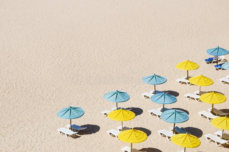 Sunbeds med paraplyer på den sandiga stranden arkivfoto