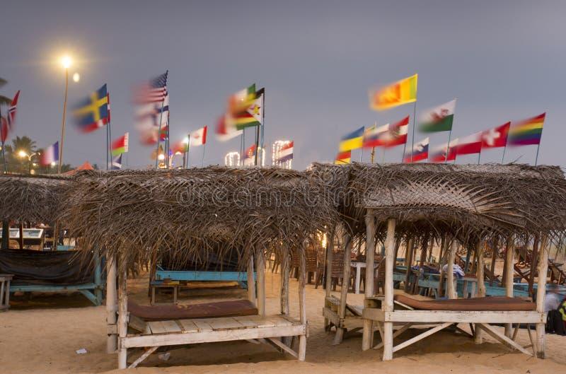 Sunbeds met stro sunshades op zandig strand royalty-vrije stock afbeeldingen