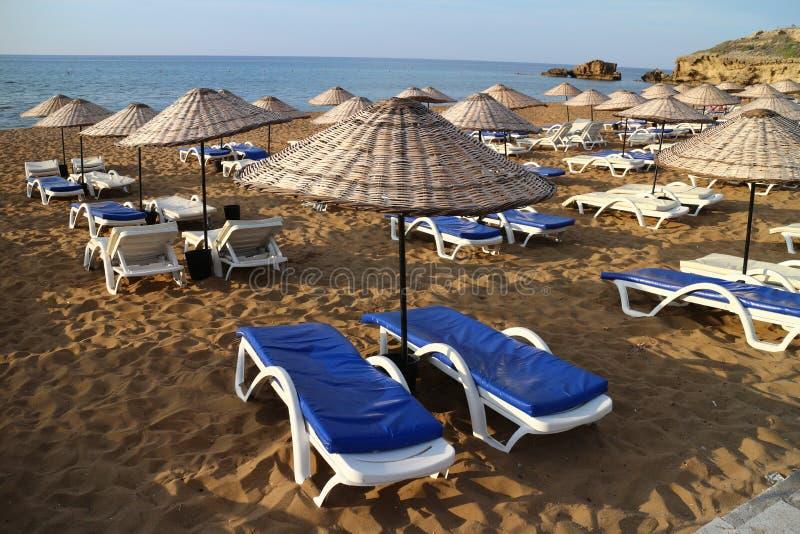 Sunbeds mit Regenschirmen auf Sand-Strand stockbilder