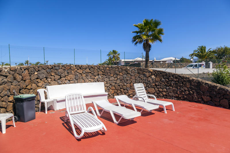 Sunbeds na área da piscina exterior tropical sem povos fotografia de stock royalty free