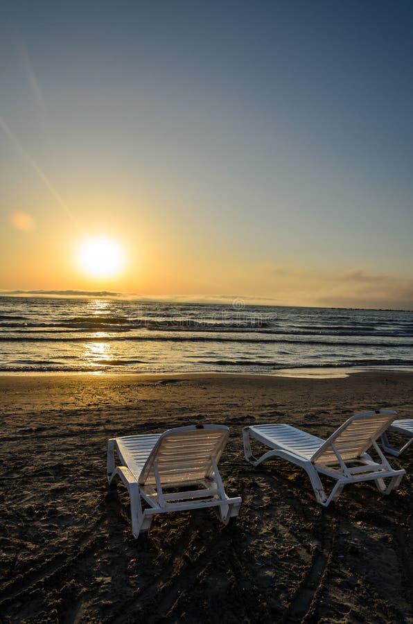 Sunbeds na praia do Mar Negro no nascer do sol, atmo morno da luz do sol foto de stock royalty free