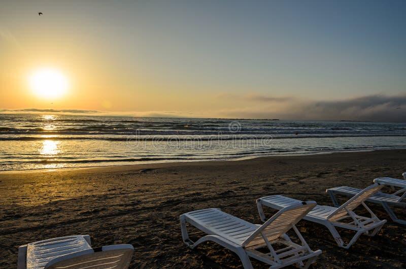 Sunbeds na praia do Mar Negro no nascer do sol, atmo morno da luz do sol imagens de stock