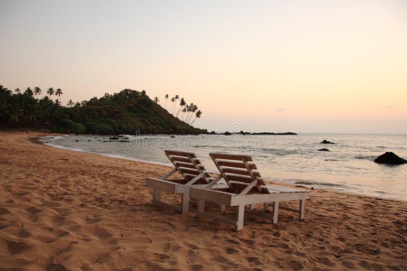 Sunbeds na praia no por do sol fotografia de stock