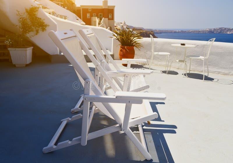 Sunbeds na tarasie hotel wzgórza budynku Greece wyspy santorini Piękny lato krajobraz z dennym widokiem obraz stock