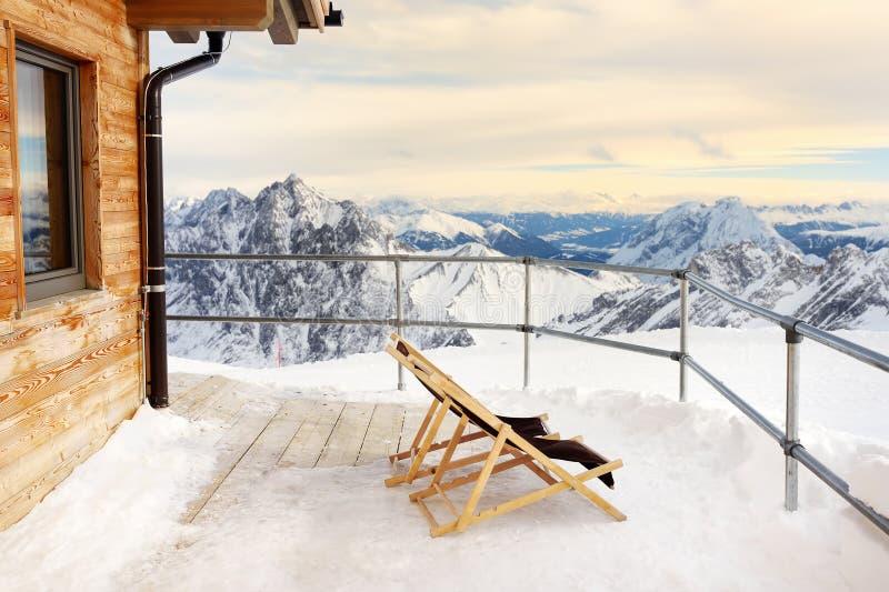 Sunbeds no terraço da casa alpina do chalé nas montanhas fotos de stock