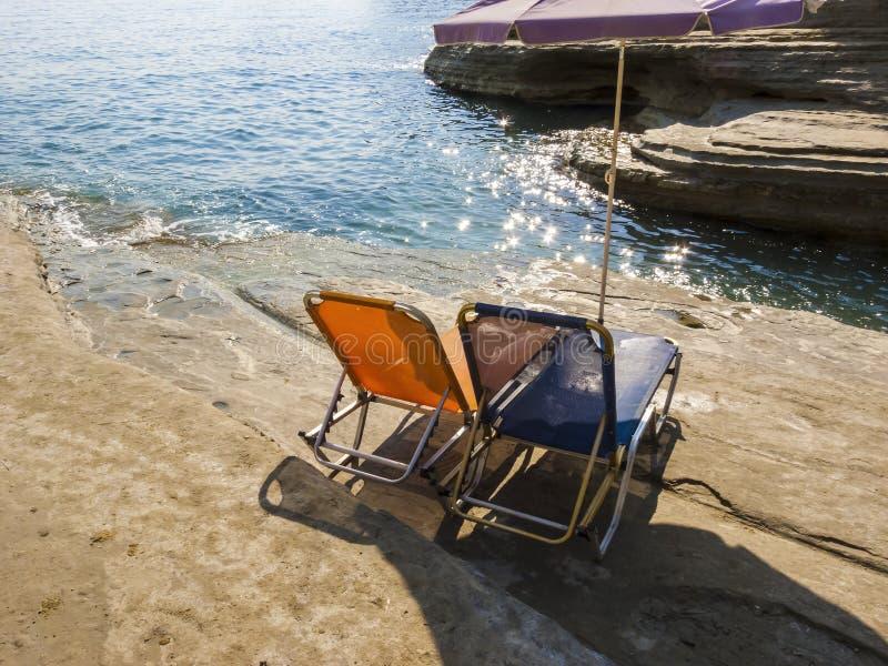 Sunbeds och paraply på den steniga stranden i den Korfu ön, Grekland fotografering för bildbyråer