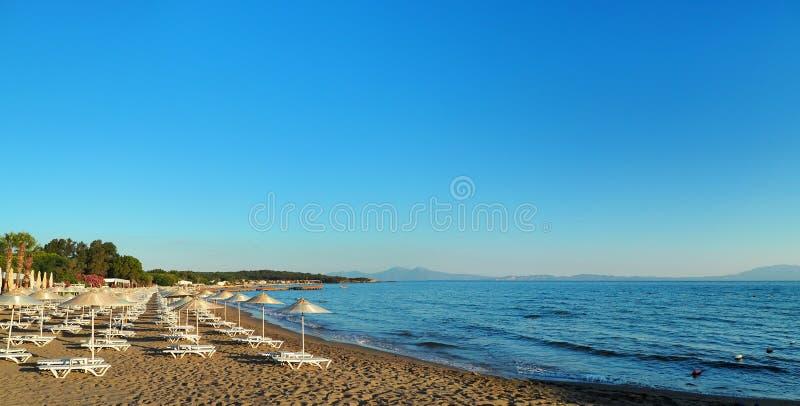 Sunbeds och paraplyer för kust Turkiet för Aegean hav på stranden royaltyfria bilder