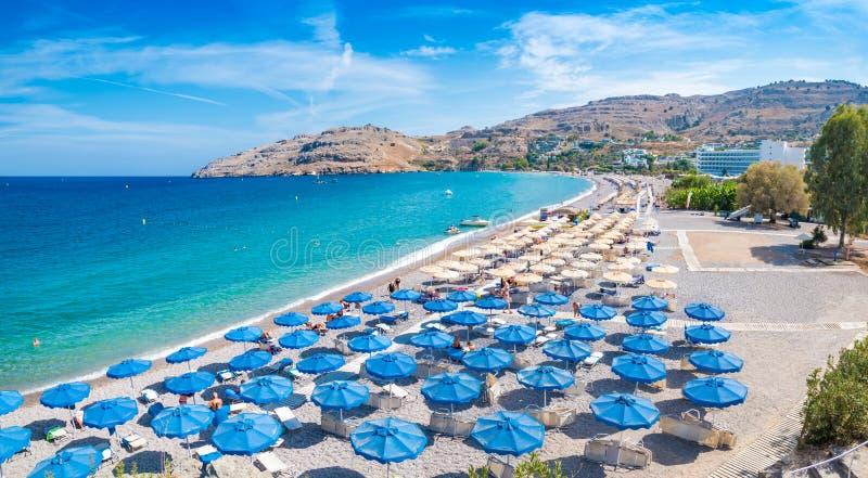 Sunbeds och paraplyer på den Vlycha stranden nära hotellsemesterorten Rhodes, arkivfoton