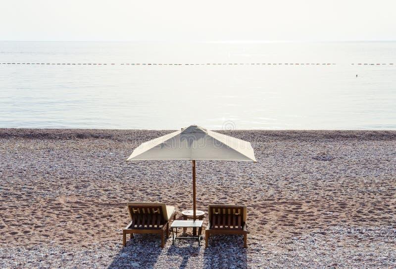 Sunbeds op zandig strand in wellustige dag, Budva Riviera, Montenegro stock foto