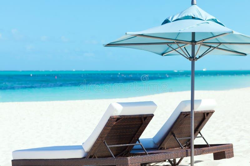 Sunbeds på stranden royaltyfria bilder
