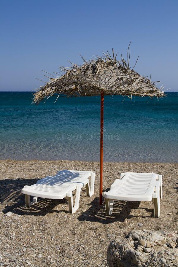 Sunbeds på stranden royaltyfria foton