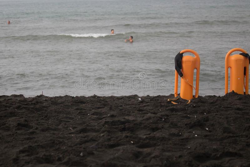 Sunbeds på strandhavet, hav Folk i havet Hjälpmedel för preserver för livräddareräddningsaktionutrustning orange, rött plast- fly royaltyfria bilder