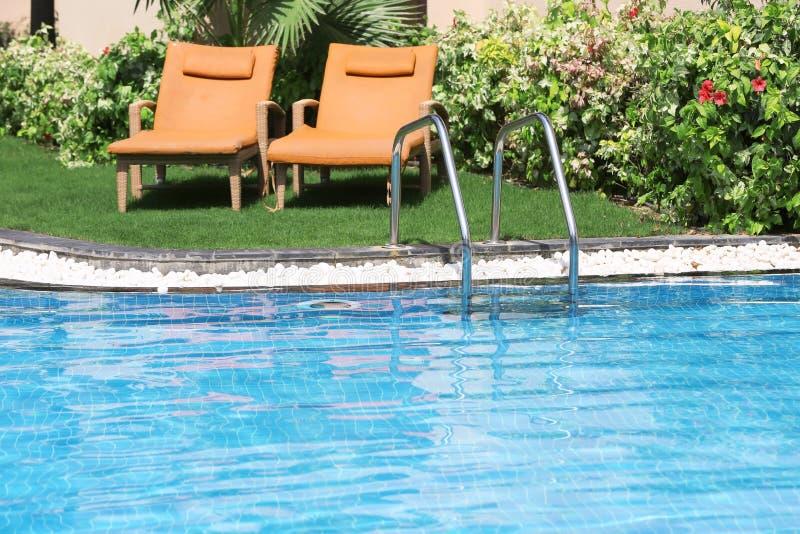 Sunbeds perto da piscina moderna com escadas, ilustração do vetor