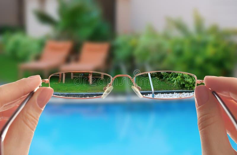 Sunbeds perto da piscina moderna com escadas fotografia de stock royalty free