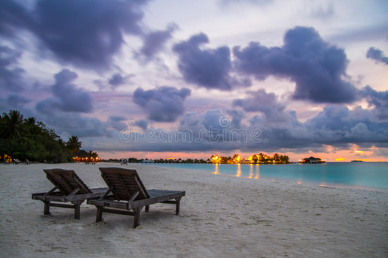 Sunbeds on a tropical beach. White sandy beach and blue lagoon after the sunset stock images
