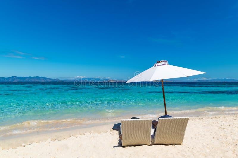 Sunbeds with umbrella on the sandy beach near the sea. stock photos
