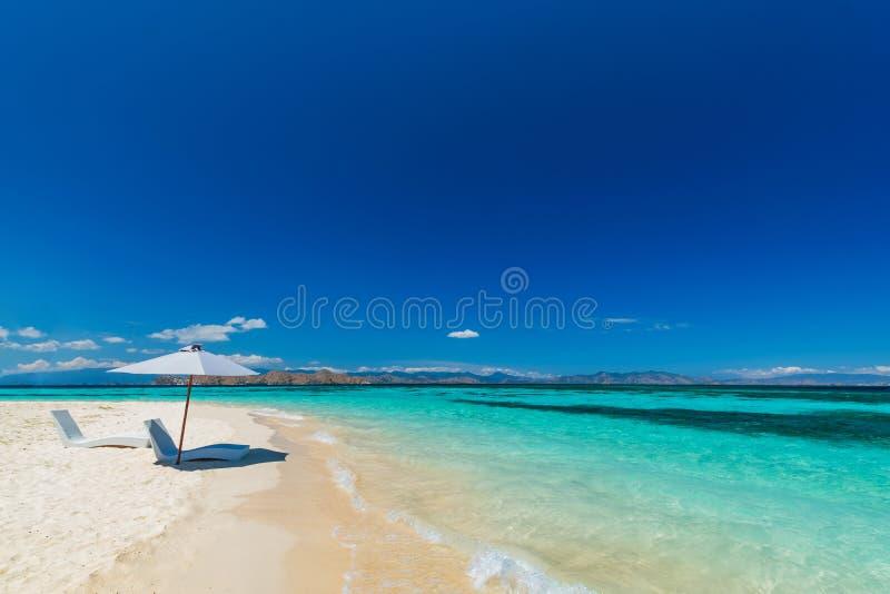 Sunbeds with umbrella on the sandy beach near the sea. stock photo