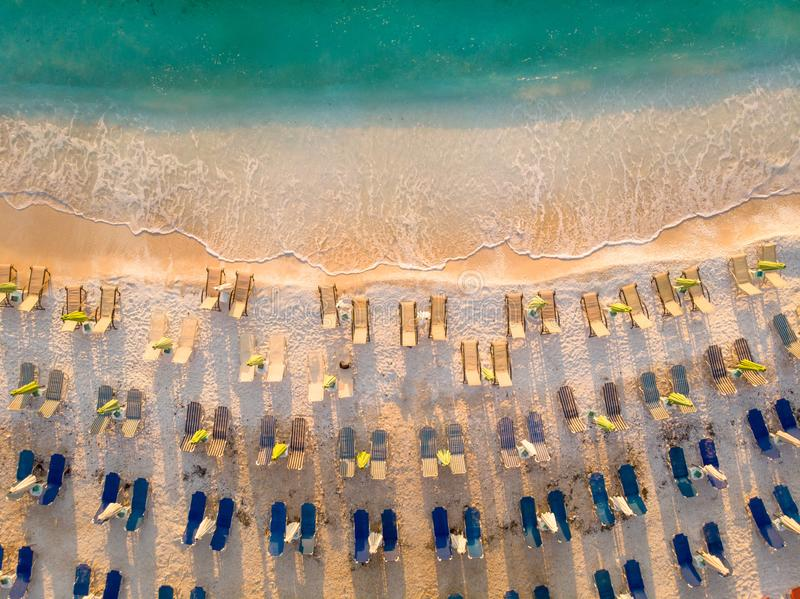 Sunbeds and umbrellas on the beach at sunrise in Thasos, Greece. Aerial image of a beach in Agean sea shot using a drone royalty free stock image