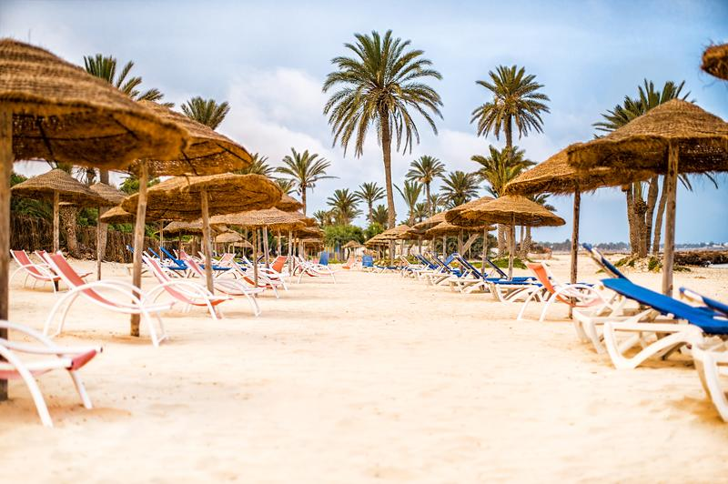 Sunbeds with parasols on snow-white sand on beach royalty free stock photos