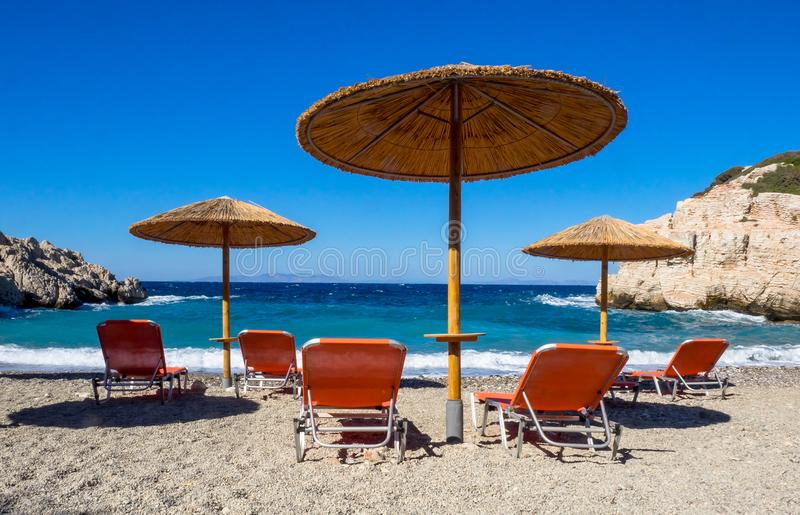 Sunbeds und Sonnenschirme auf dem Strand von Griechenland lizenzfreie stockfotografie