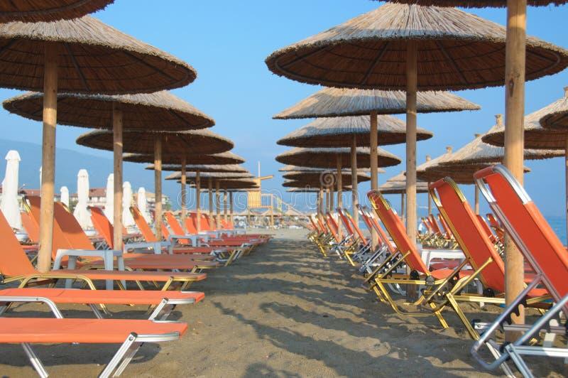 Sunbeds und Sonnenschirme auf Strand lizenzfreie stockfotos