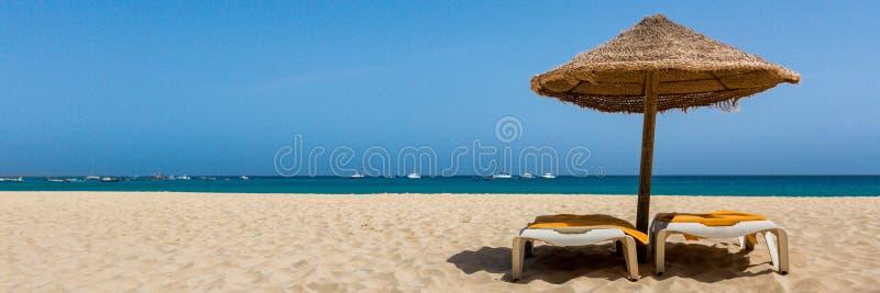 Sunbeds under paraplyet på stranden royaltyfri foto