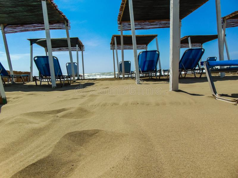 Sunbeds under straw sunshades on the empty sandy beach. stock photo