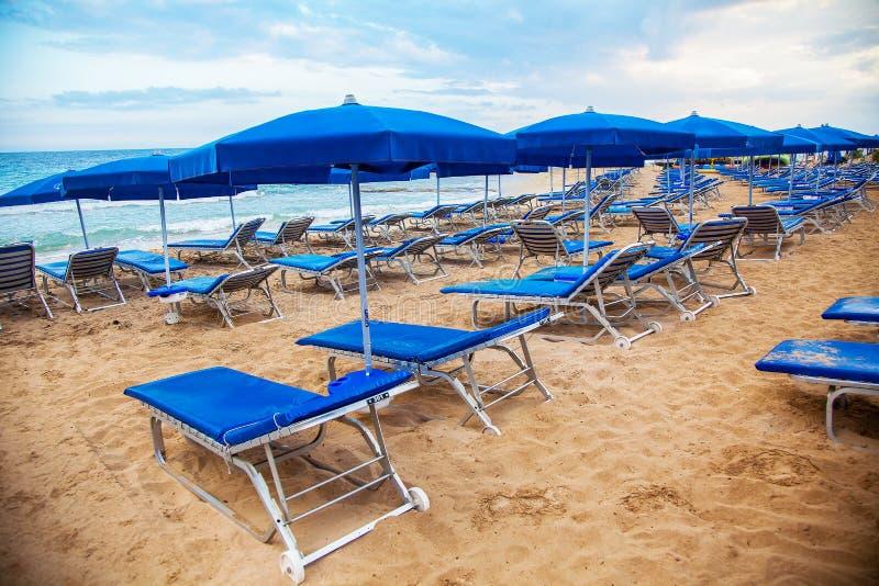 Sunbeds vacíos azules con los paraguas en la playa fotos de archivo