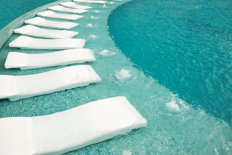 Sunbeds vacíos por la piscina del centro turístico imágenes de archivo libres de regalías