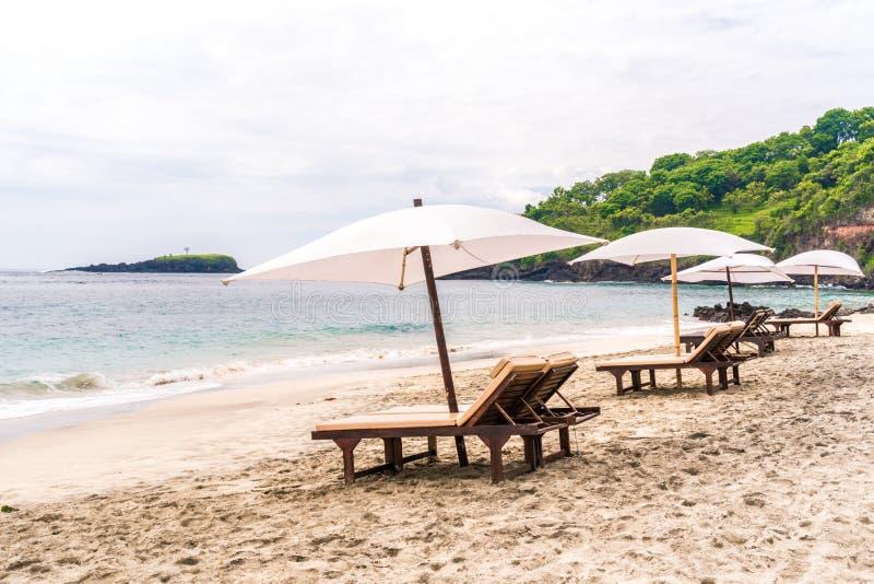 Sunbeds vac?os que esperan turistas en la playa o Pasir Putih de la Virgen o la playa en Bali, Indonesia de Perasi Tropical hermo fotografía de archivo