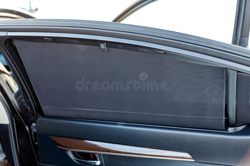 Sunblind on the glass of the rear door of the car black color close-up protects from the sun rays textured double mesh of a royalty free stock photo