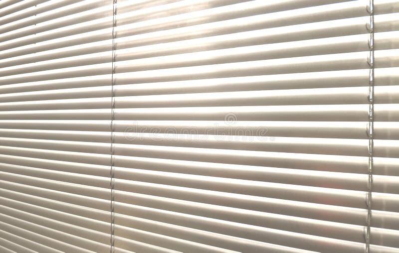 Sunblinds metálicos cinzentos do jalusie da janela imagem de stock