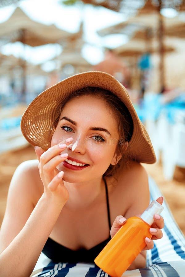 Sunblock della protezione solare Donna che mette crema solare giorno di estate sorridente del naso il bello Skincare Ragazza che  fotografia stock libera da diritti