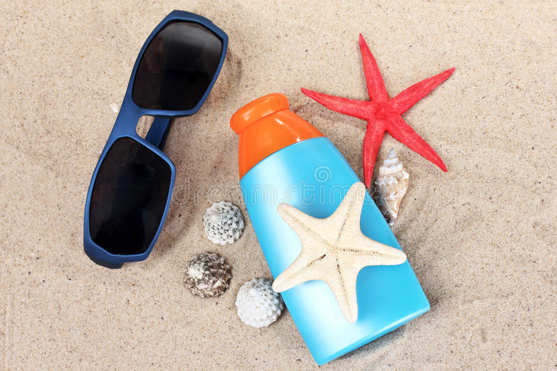 Sunblock, gafas de sol, shelles y estrellas de mar fotografía de archivo libre de regalías