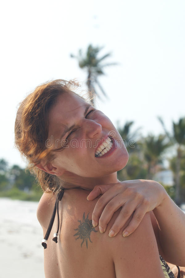 Sunburn. Young woman on a beach is holding her back in pain. She has a sunburn royalty free stock photo