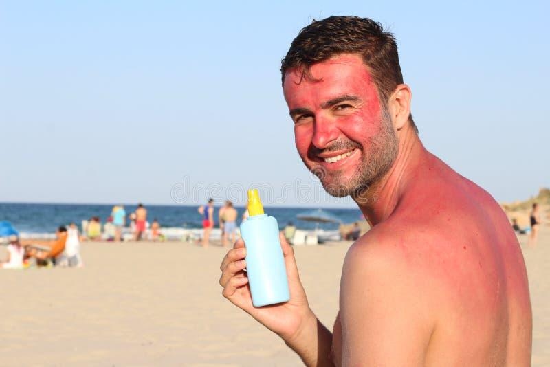Sunburned man using tanning accelerator lotion royalty free stock photos