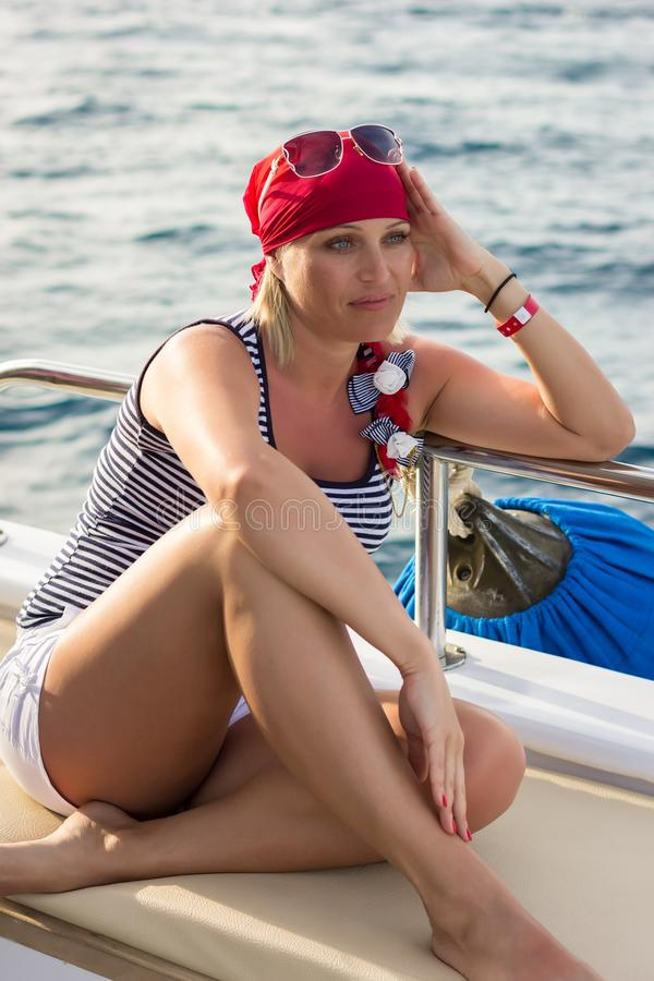 Sunburnt girl sits on a leather couch on a yacht and looks into the distance royalty free stock image