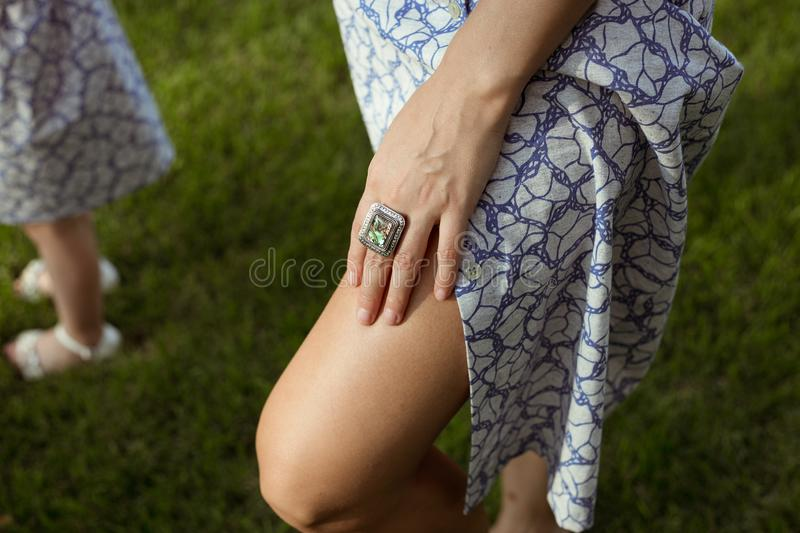 Sunburnt women legs in summer cloth and hand stock image