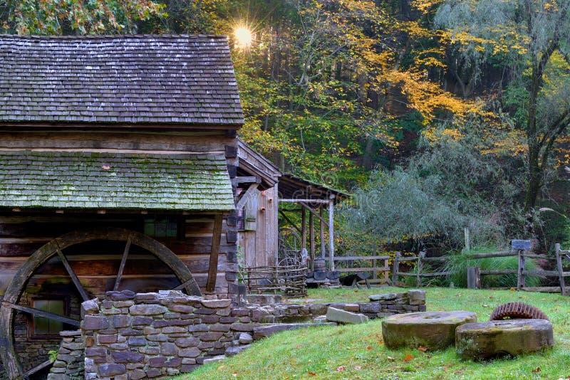 Sunburst no nascer do sol com o moinho histórico velho da munição no foregrou fotografia de stock