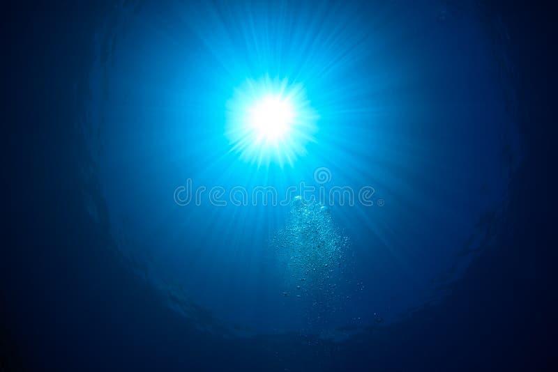 Sunburst och bubblor på havyttersidan royaltyfri bild
