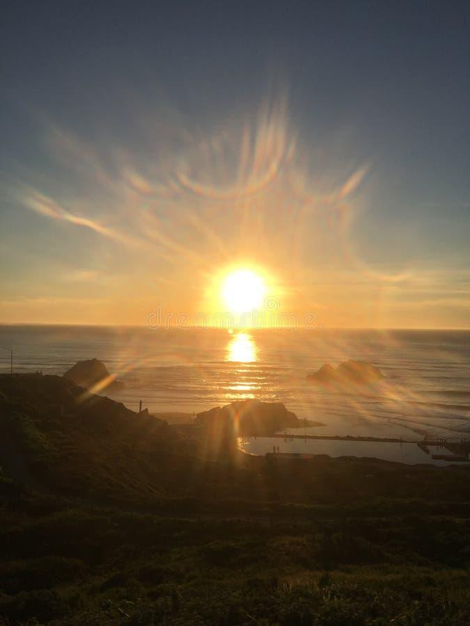 Sunburst på havstranden arkivbilder