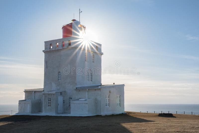 Sunburst shining through the Dyrholaey Lighthouse in Iceland. With the Atlantic Ocean in the background stock photo