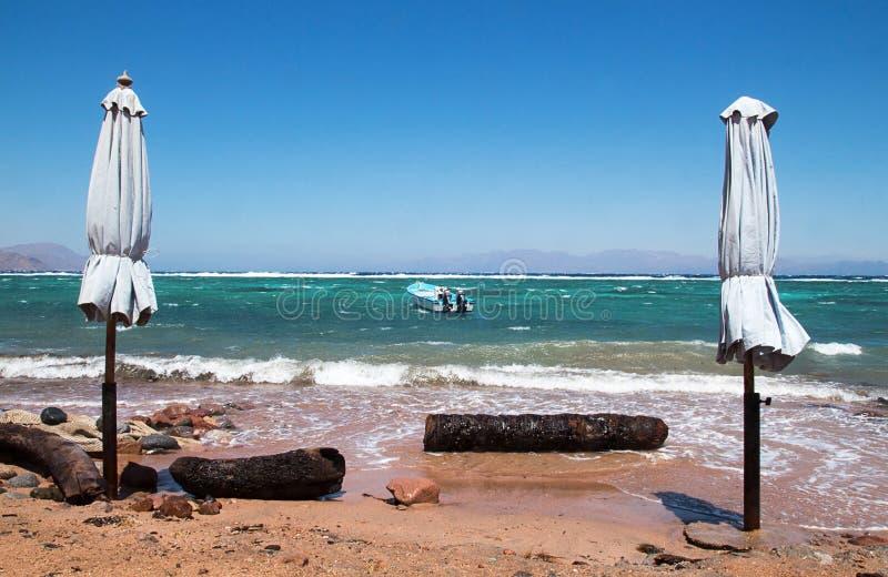 Sunchades fechados na praia Mar Vermelho do Seascape, Dahab, Sinai, Egito fotografia de stock