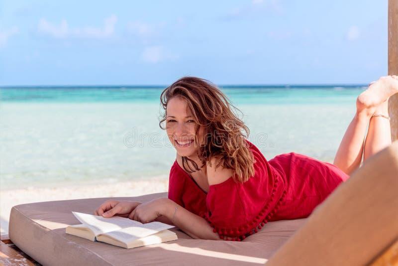 sunchair的妇女读一本书的在一个热带地点 作为背景的清楚的绿松石水 库存照片