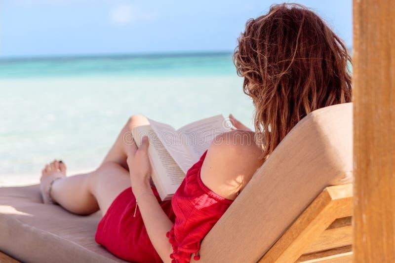 sunchair的妇女读一本书的在一个热带地点 作为背景的清楚的绿松石水 免版税图库摄影