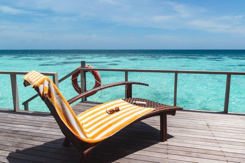Sunchair med handduken på en terrass över klart blått vatten under en solig dag royaltyfri fotografi