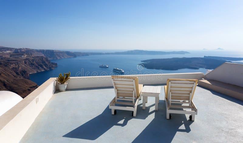 Sunchairs che affronta la caldera di Santorini fotografia stock