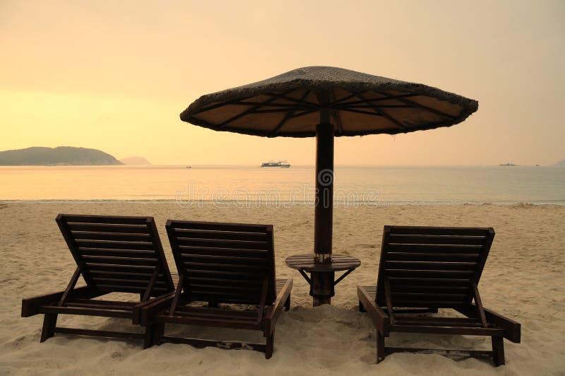 Sunchairs en paraplu's op het strand bij zonsopgang royalty-vrije stock afbeeldingen