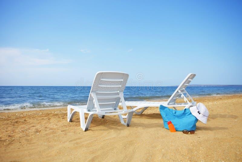 Sunchairs i Pakująca plażowa torba na pustej piasek plaży obraz royalty free
