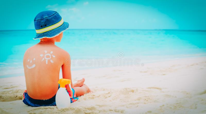 Мальчик предохранения от Солнца с suncream на пляже стоковое фото rf